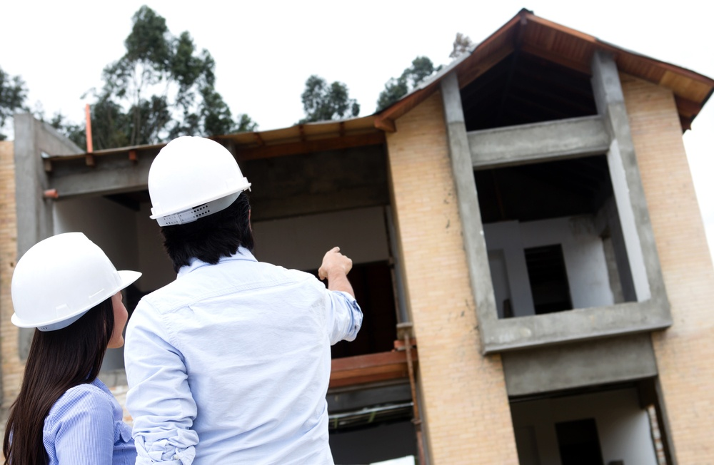 Architects at a construction site pointing at a house.jpeg