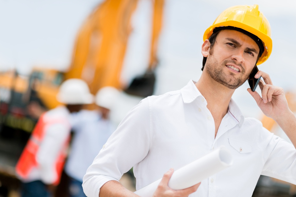 Engineer at a construction site making a business call .jpeg